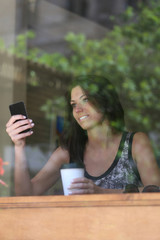 Girl using cellphone while drinking coffee