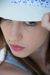 Pretty Greek teenager wearing a hat with serious face