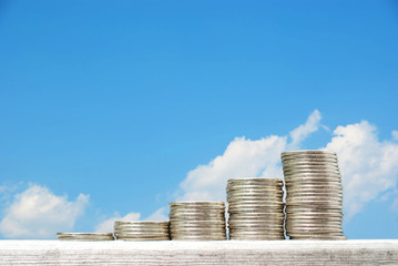 Business concept with stacks of coins against blue sky backgroun