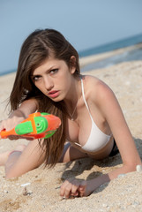 Pretty greek young women playing water gun at the beach