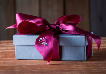 Holiday Gift Packed into Grey Box with Purple Ribbon on Rustic W