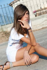 Nice looking light brunette sitting down on the street