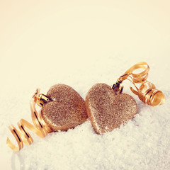 Two hearts with gold tapes on snow