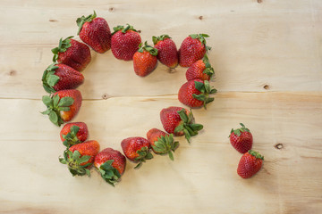 Fresh strawberries heart on old wooden background
