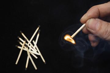 Hand holding burning match stick on black background