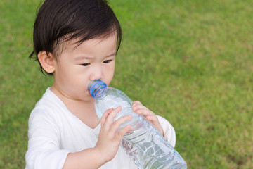 Little asian girl  drinking water from plastic bottle