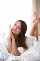Beautiful happy smiling young woman in bed