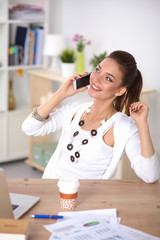 Young businesswoman sitting at the desk and talking on phone