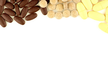 Multi colored pills scattered on white background with aerial vi