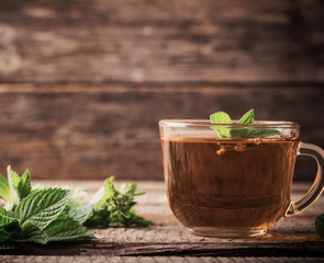 cups of tea with mint on wooden