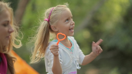 Little girl with her family blowing soap bubbles and laughing