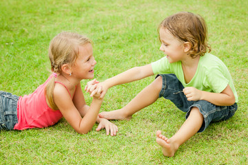 two happy children playing on the grass at the day time