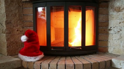 Santa Claus red hat in front of the fireplace