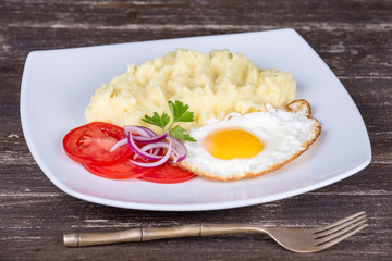 Mashed potatoes with fried eggs and tomato