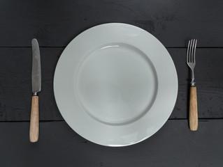 Besteck und Teller auf schwarzem Holzhintergrund