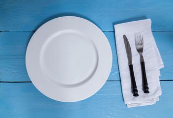 Besteck und Teller auf blauem Holzhintergrund