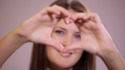 Girl makes the shape of a heart with her hands