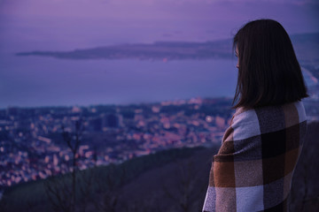 Woman wrapped in plaid looking at the city in evening