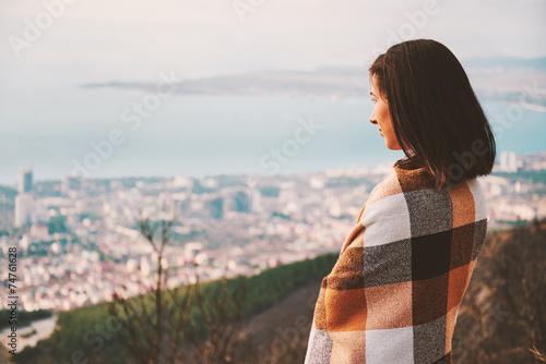 Kobieta zawijająca w szkockiej kraty patrzeje miasto w jesieni