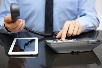 businessman is calling support when reading report on tablet com
