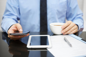 Businessman is using smart phone and reading email on tablet pc