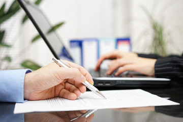 businessman is examine document and woman is working on laptop c