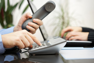 businessman and woman are contacting new clients  over telephone
