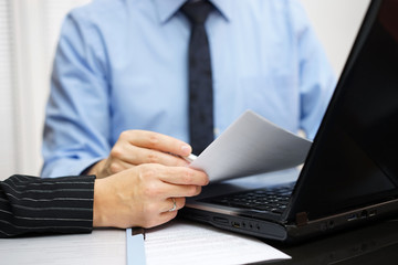 Consultant and client are working with documents and laptop on o