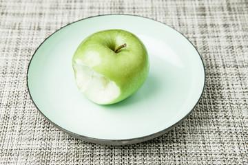 Angebissener grüner Apfel auf Teller