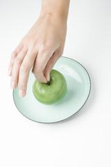 Hand hölt grünen Apfel über Teller
