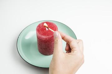 Hand zündet Kerze auf Teller an