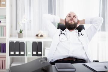 Arzt sitzt am Schreibtisch in seiner Praxis und grübelt