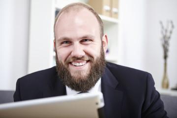 Geschäftsmann liest etwas auf seinem Tablet Computer
