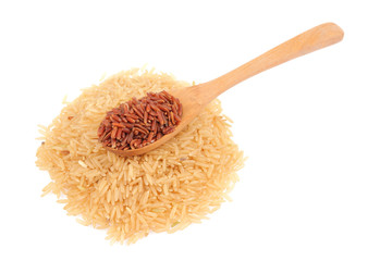 Red rice in a wooden spoon and pile of brown rice