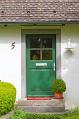 Grüne Wohnungstür an einem Landhaus