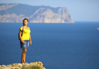 woman on top of a mountain above the sea