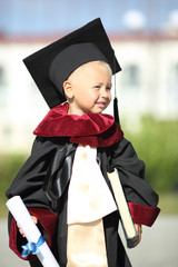 funny kid dressed as a graduate of the University