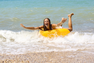 laughing girl in bikini on inflatable ring