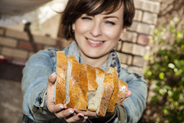Young positive woman with fresh sliced bread