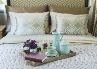 Decorative tray with book,tea set and flower on the bed