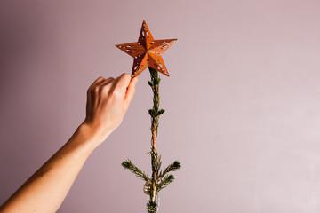 Hand putting star on christmas tree