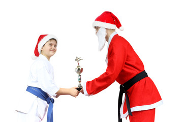 Santa Claus is giving the sportsman in karategi the cup karate