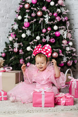 Little girl rejoices gifts near a Christmas tree
