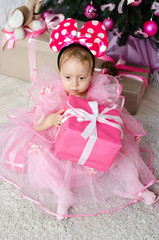 Little girl in a beautiful dress is holding a Christmas gift