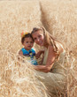 Mother with the little daughter in the field of ripe wheat
