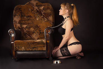 sexy female slave sits next to the chair