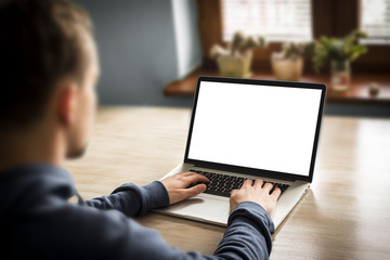 Man using notebook with blank screen, in home interior.