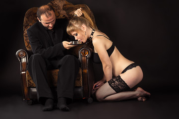 man feeding slave girl milk to the bowl