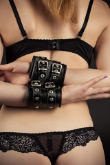 female slave in leather handcuffs in underwear