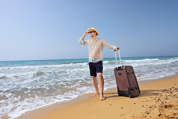 Lost young tourist with his baggage on a beach